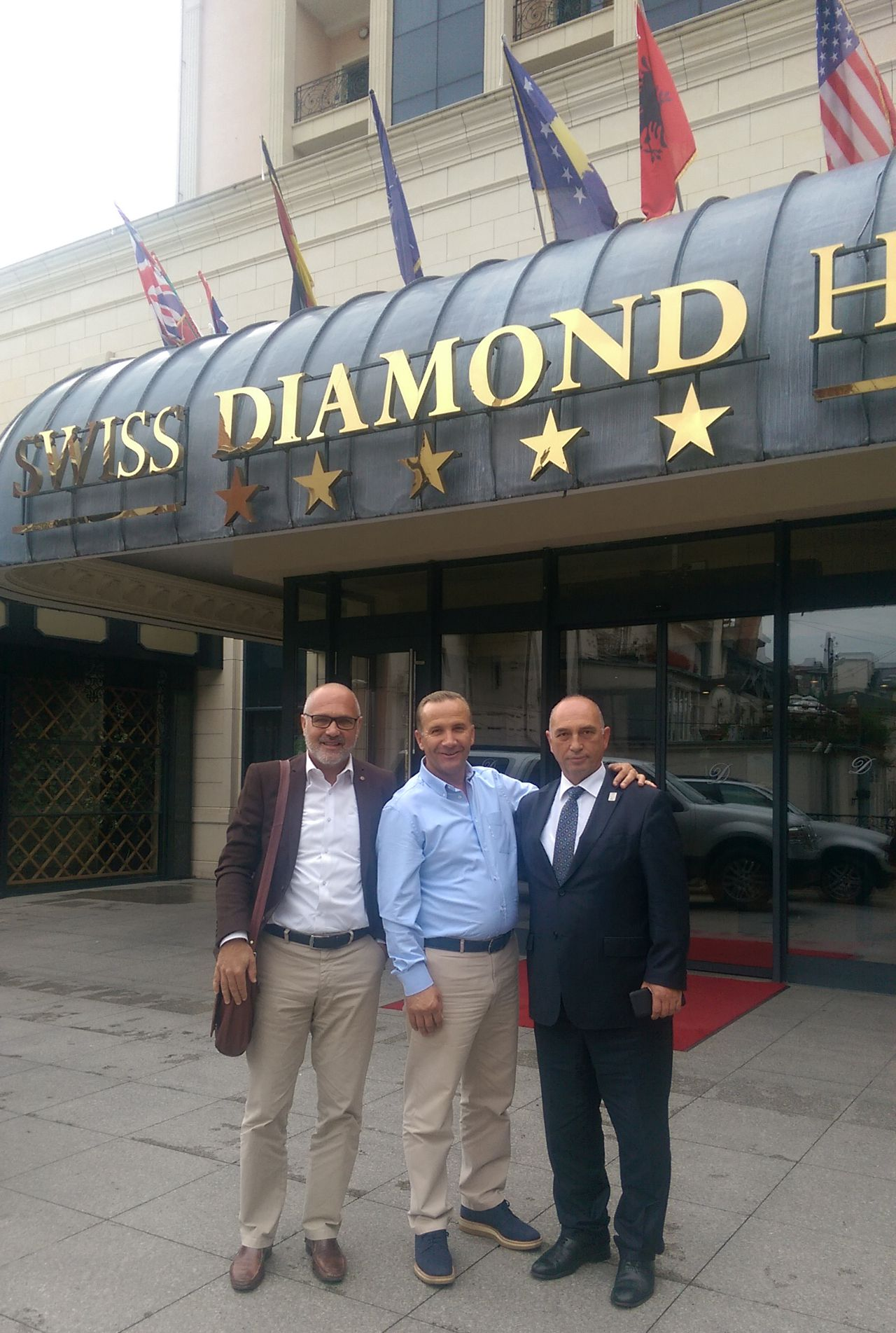Damjan Pintar with partners in front of a hotel