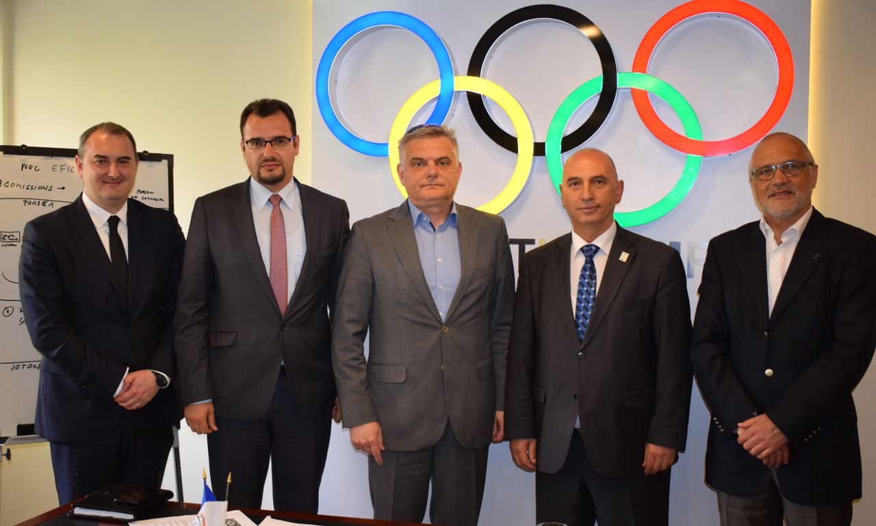 men posing for a picture in front of the olympic logo
